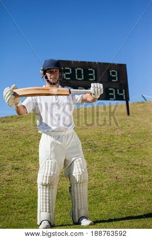 Full length of confident cricketer holding bat while standing on field