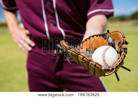 Mid section of baseball pitcher showing ball in glove at playing field