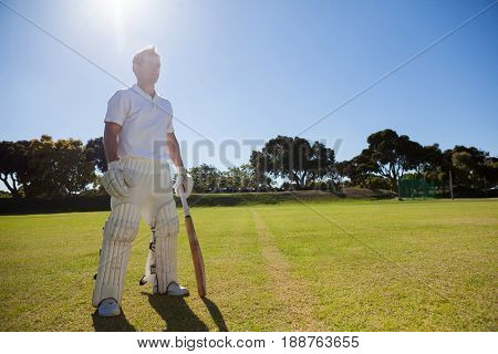 Full length of cricket player with bat standing on grassy field on sunny day