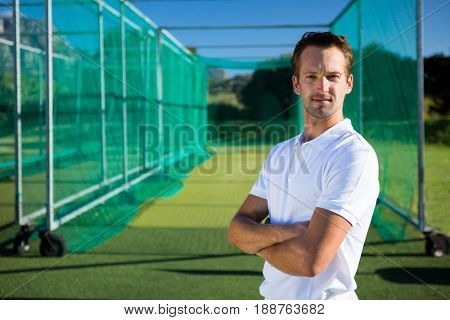 Portrait of young cricketer with arms crossed standing against net on field