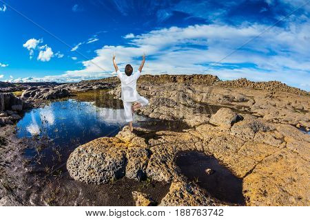 Small picturesque pool, which reflects the blue sky. Photo taken fisheye lens. Middle-aged woman standing in pose