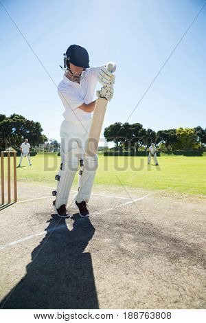 Full length of batsman standing on pitch against clear sky
