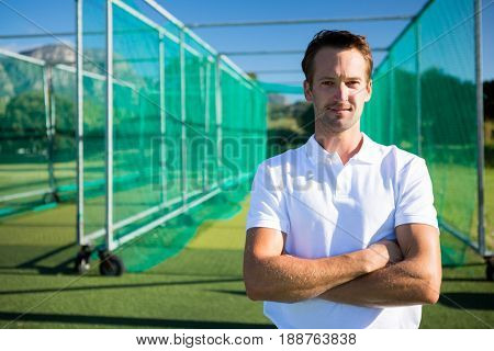 Portrait of young cricketer standing with arms crossed against net on field