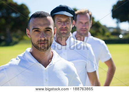Portrait of cricket players standing at grassy field on sunny day