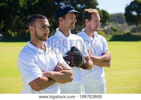 Confident cricket players standing at grassy field on sunny day