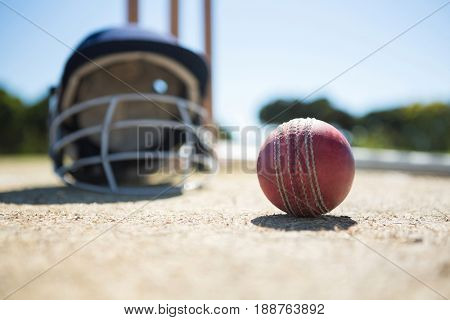 Close up of cricket ball with helmet on pitch during sunny day