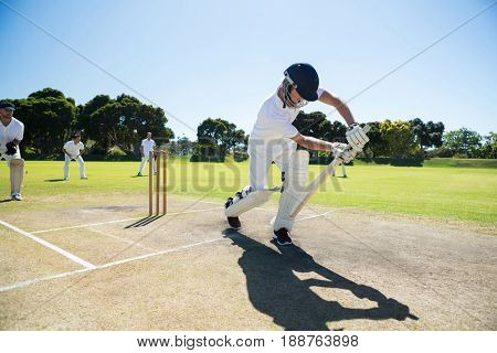 Young man playing cricket at field against clear sky on sunny day