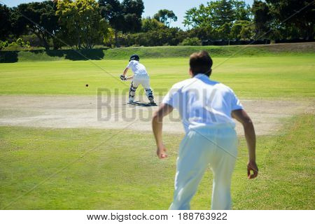 Rear view of men playing cricket at pitch on sunny day