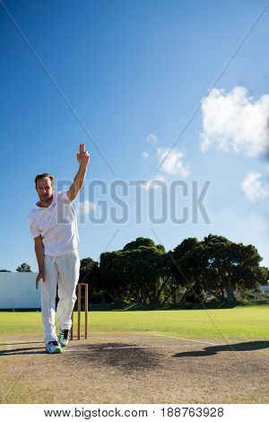 Full length of man bowling while standing on cricket field against sky