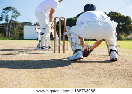 Rear view of wicket keeper crouching by stumps during match on sunny day