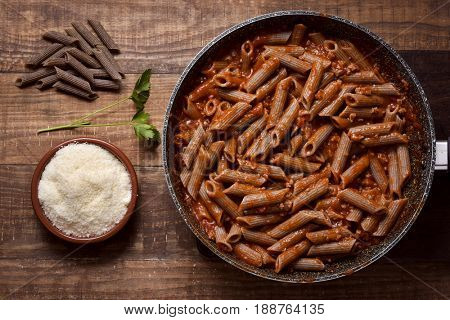 high-angle shot of a frying pan with buckwheat penne rigate alla bolognese, a bunch of uncooked buckwheat penne rigate and an earthenware bowl with grated Parmigiano cheese, on a rustic wooden table