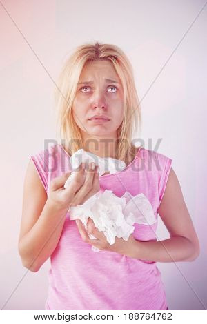 Young woman suffering from cold looking up while holding tissues against gray background