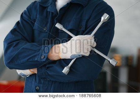 Auto mechanic with wheel wrench in car repair shop, closeup