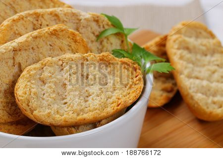 bowl of crispy rusks on wooden cutting board - close up