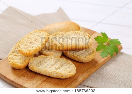 pile of crispy rusks on wooden cutting board - close up