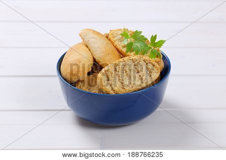 bowl of crispy rusks on white wooden background