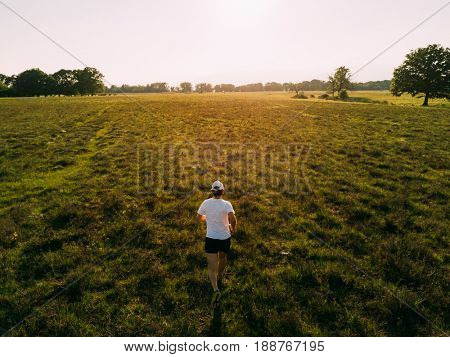 A man runs in the countryside at sunset. Back view, young caucasian male, white t-shirt. Summer season.