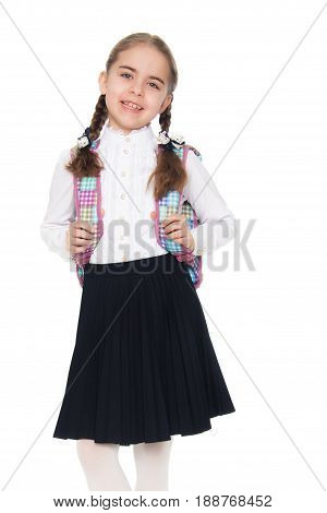 Beautiful little blond schoolgirl, with long neatly braided pigtails. In a white blouse and a long dark skirt.She wears a school satchel.Isolated on white background.