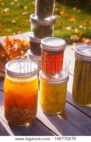 Jars of home canned food on a wooden table in autumn