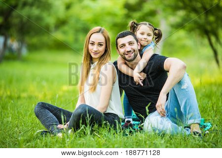Happiness And Harmony In Family Life. Happy Family Concept. Young Mother And Father With Their Daugh