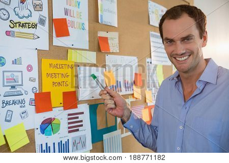 Portrait of male executive looking at bulletin board in office