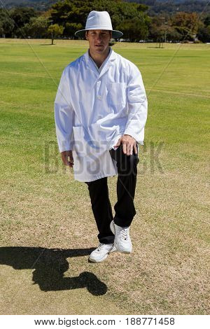 Portrait of cricket umpire signaling leg bye on sunny day during match
