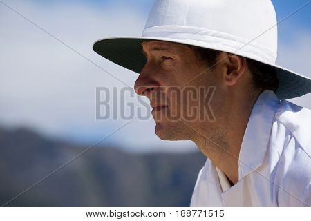 Side view of focused umpire against sky during cricket match on sunny day