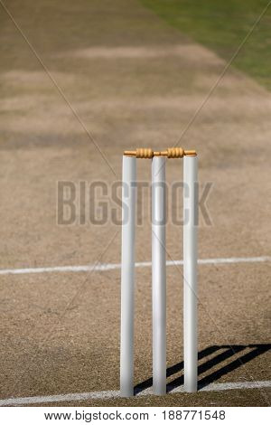 High angle view of white stumps on cricket field during sunny day