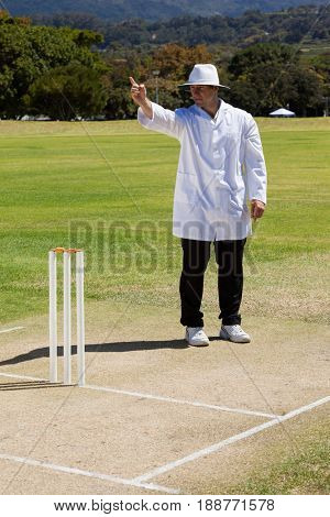 Full length of cricket umpire signalling out during match on sunny day against clear sky