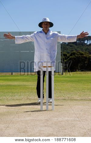 Full length of cricket umpire signalling wide ball during match against clear sky on sunny day