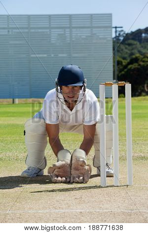 Portrait of wicketkeeper crouching behind stumps on field during sunny day