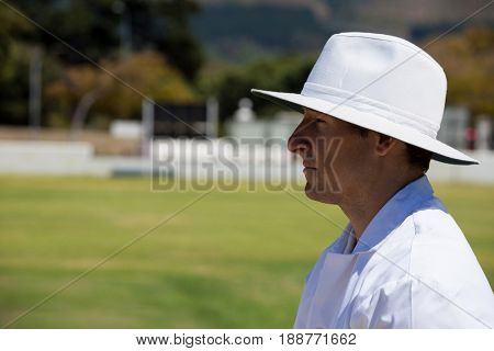 Profile view of umpire standing at field during cricket match on sunny day