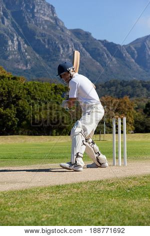 Side view of cricket player playing on field during sunny day
