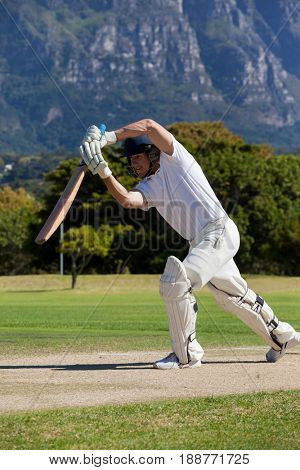 Cricket player playing on field against mountain during sunny day