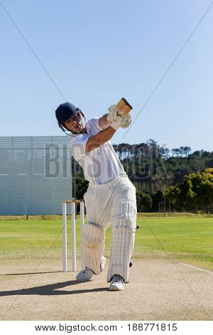 Full length of cricket player batting on field against clear sky