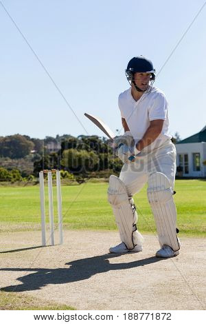 Cricket player batting on pitch against clear sky during sunny day