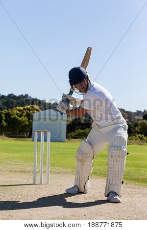 Full length of determined cricketer playing on field during sunny day