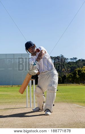 Confident player playing cricket on field against clear blue sky