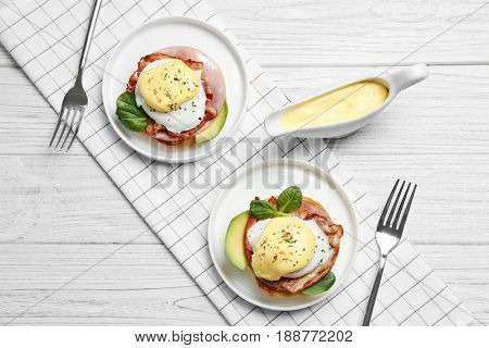 Tasty eggs Benedict on plates, top view