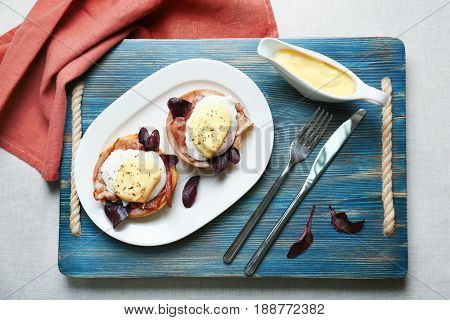 Tasty eggs Benedict with sauce on plate