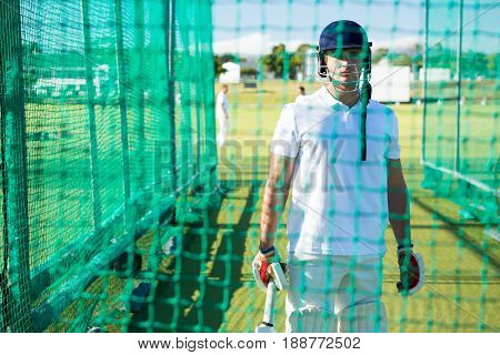Portrait of confident cricket player wearing helmet standing at pitch