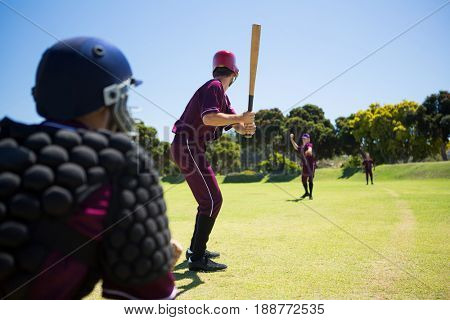 Players playing baseball together on field against clear blue sky