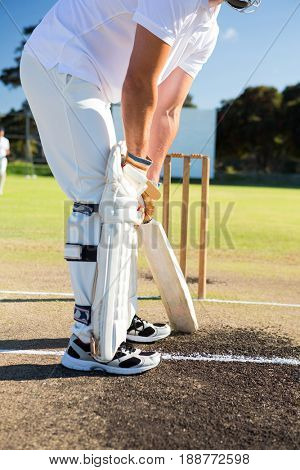 Low section of man playing cricket at sports field on sunny day