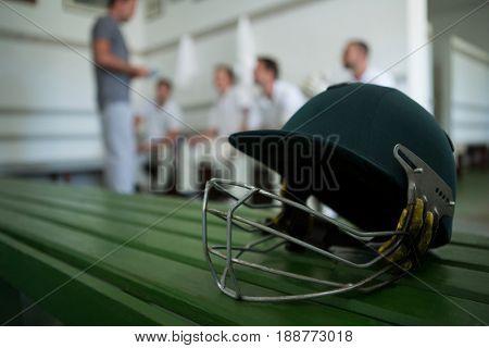 Close up of cricket helmet on table against team in locker room