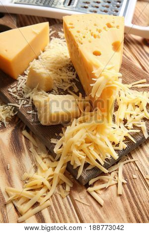 Cutting board with cheese and grater on wooden background