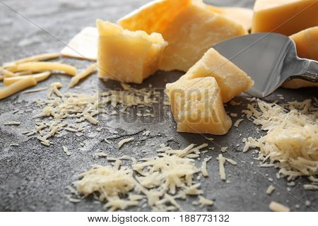 Pieces of cheese and shovel on grey background