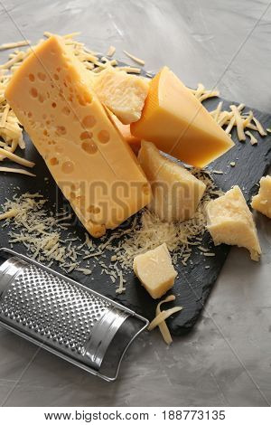 Slate plate with cheese and grater on light background