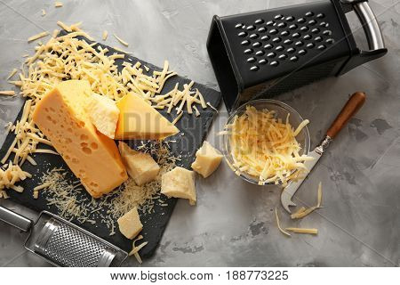 Slate plate, bowl with cheese, graters and knife on grey background