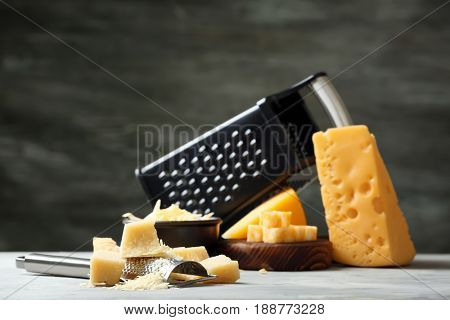 Grater and pieces of cheese on grey background