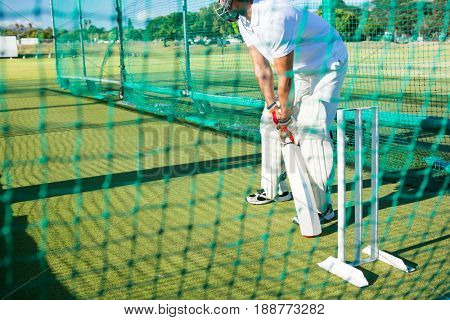 Low section of man playing cricket at field on sunny day